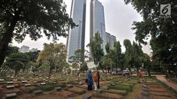 Warga berziarah di salah satu makam di TPU Karet Bivak, Jakarta, Kamis (12/7). DKI Jakara saat ini hanya memiliki 38,3 hektare lahan yang siap pakai untuk pemakaman. (Merdeka.com/Iqbal Nugroho)