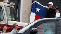 Presiden AS, Donald Trump mengibarkan bendera Texas di hadapan warga yang bersorak padanya di Firehouse 5 in Corpus Christi, Selasa (29/8). Trump mencoba menyemangati warganya lewat kunjungan ke Texas yang dihantam badai Harvey. (AP Photo/Evan Vucci)