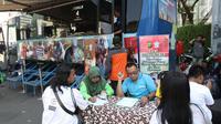 Warga mengisi formulir pajak kendaraan bermotor di gerai Samsat Keliling Car Free Day, Jakarta, Minggu (21/10). Layanan pembayaran pajak Surat Tanda Nomor Kendaraan (STNK) bisa dilakukan tanpa membawa salinan atau BPKB. (Liputan6.com/Angga Yuniar)