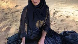 Tania Nadira yang mewarisi darah Arab membuat wajahnya punya ciri khas tersendiri. Sepupu dari Tasya Farasya itu selalu terlihat cantik dalam busana apapun. Ibu muda dua anak ini pun tampak memesona ketika mengenakan hijab hitam sambil berpose duduk di hamparan pasir. (Liputan6.com/IG/@tanianadiraa)