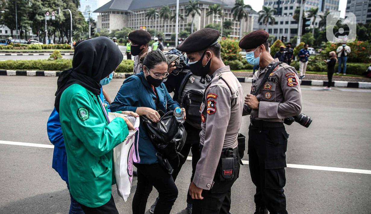 Polisi memeriksa barang bawaan mahasiswa yang akan berunjuk rasa di Patung Kuda, Jakarta, Selasa (20/10/2020). Pemeriksaan tersebut dilakukan untuk memastikan unjuk rasa berjalan aman dan damai. (Liputan6.com/Faizal Fanani)