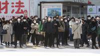 Orang-orang memakai masker untuk melindungi dari penyebaran virus corona menunggu di persimpangan di Tokyo (8/2/2021).  Jumlah infeksi virus corona di Ibu Kota Tokyo, Jepang, meningkat sampai sembilan kali lipat sejak akhir musim panas lalu. (AP Photo/Eugene Hoshiko)