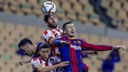 Pemain Athletic Bilbao, Raul Garcia, duel udara dengan pemain Barcelona, Clement Lenglet, pada laga final Piala Super Spanyol di Stadion La Cartuja, Minggu (17/1/2021). Athletic Bilbao menang 3-2 atas Barcelona. (AP/Miguel Morenatti)