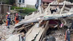 Tim penyelamat berusaha mencari korban di reruntuhan sebuah apartemen tua yang ambruk di Swiebodzce, Polandia, Sabtu (8/4). Pemadam kebakaran dan anjing pelacak masih mencari korban hilang di antara reruntuhan bangunan. (Natalia DOBRYSZYCKA/AFP)
