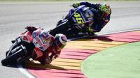 Pembalap Ducati Team, Jorge Lorenzo (depan) bersaing dengan pembalap Movistar Yamaha, Valentino Rossi pada balapan MotoGP Aragon di Spanyol, Minggu (24/9). Rossi kembali dan tampil di MotoGP Aragon usai jalani pemulihan selama 25 hari. (JOSE JORDAN/AFP)