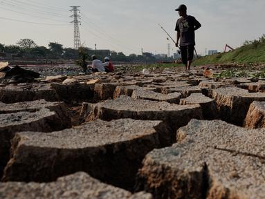 Warga bersiap memancing di sekitar Kanal Banjir Barat (KBB) yang mengalami kekeringan di kawasan Tanah Abang, Jakarta, Jumat (12/7/2019). Musim kemarau yang terjadi di Ibu Kota menyebabkan debit air di KBB berkurang sehingga menimbulkan keretakan tanah di sekitarnya. (Liputan6.com/Immanuel Antonius)