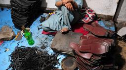 """Seorang pembuat sepatu asal Pakistan beristirahat setelah membuat sepatu tradisional yang dikenal sebagai """"chapli"""" di kalangan penduduk lokal untuk menyambut Hari Raya Idul Fitri di Peshawar, Pakistan barat laut, pada 19 Mei 2020. (Xinhua/Saeed Ahmad)"""