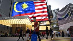 Orang-orang yang memakai masker menyeberang jalan di luar pusat perbelanjaan, di tengah wabah COVID-19 di Kuala Lumpur, Malaysia, Selasa (14/9/2021). Kementerian Kesehatan Malaysia melaporkan total kasus Covid-19 mencapai 2.011.440 pada hari ini, Selasa (14/9). (AP Photo/Vincent Thian)