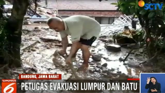 Petugas gabungan dari polisi dan TNI dibantu warga terus berupaya mengevakuasi kendaraan pribadi yang rusak akibat terjangan banjir.