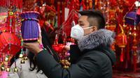 Seorang pria berbelanja dekorasi untuk perayaan Tahun Baru  Imlek di sebuah pasar di Provinsi Anhui, China, 23 Januari 2020. China menutup sebuah kota berpenduduk lebih dari 11 juta orang dalam upaya memerangi wabah virus corona, tindakan yang belum pernah terjadi sebelumnya.  (AP/Mark Schiefelbein)