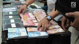 Petugas merapikan uang barang bukti Tindak Pidana Perdagangan Orang saat rilis di Bareskrim Mabes Polri, Jakarta, Senin (23/4). Bareskrim Mabes Polri menahan delapan tersangka kasus Tindak Pidana Perdagangan Orang. (Liputan6.com/Helmi Fithriansyah)