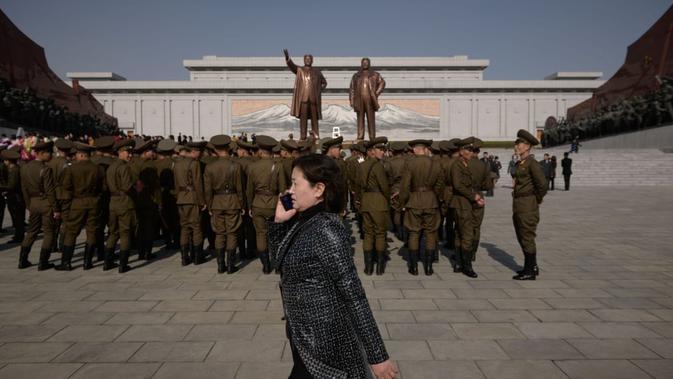Seorang wanita berbicara di ponsel ketika tentara Tentara Rakyat Korea Utara tengah bersiap-siap (AFP)