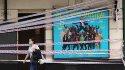 Seorang wanita berjalan melewati Apollo Theater yang disegel, London, Inggris, Selasa (7/7/2020). Pemerintah Inggris akan menyalurkan paket bantuan sebesar 1,57 miliar poundsterling kepada industri seni, budaya, dan warisan untuk membantu mengatasi dampak pandemi COVID-19. (Xinhua/Tim Ireland)