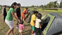 Anak-anak mencoba masuk ke dalam tenda saat persiapan untuk doa bersama pada malam Tahun Baru di Cipinang Melayu, Jakarta, Minggu (30/12). Warga Cipinang Melayu juga akan menyalakan 2.019 lilin pada malam Tahun Baru. (Merdeka.com/ Iqbal S. Nugroho)