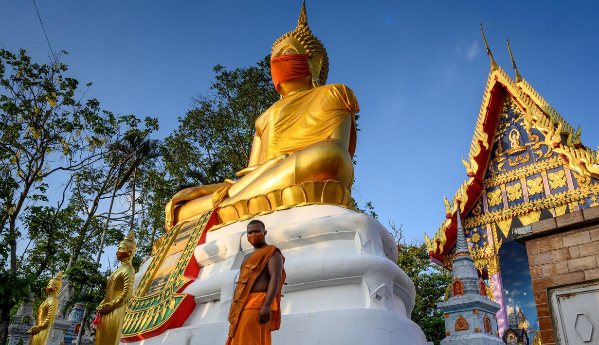 Biksu berjalan di depan patung Buddha raksasa yang mengenakan masker di kuil Wat Nithet Rat Pradit di Pathum Thani di luar Bangkok, Thailand, 12 Mei 2020. Pemasangan masker tersebut sebagai tanggapan terhadap penyebaran pandemi Covid-19. (Photo by Mladen ANTONOV / AFP)
