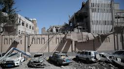 Kondisi bangungan dan mobil yang rusak parah usai terjadi serangan udara di kompleks kepresidenan, di Sanaa, Yaman (7/5). Sebelumnya kompleks kepresidenan ini telah dikuasai oleh kelompok pemberontak Houthi. (AP Photo/Hani Mohammed)
