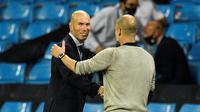 Pelatih Real Madrid, Zinedine Zidane berjabat tangan dengan manajer Manchester City, Pep Guardiola di Etihad Stadium pada leg kedua 16 besar Liga Champions 2019/2020, Sabtu (8/8/2020). (AFP/Peter Powell)