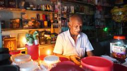 Seorang pria bekerja dengan bantuan lilin di toko miliknya di tengah pemadaman listrik di Kolombo, Sri Lanka (17/8/2020). Sri Lanka mengalami pemadaman listrik berskala nasional pada Senin (17/8) karena kerusakan teknis di sebuah pembangkit listrik di Kerawalapitiya. (Xinhua/A. Hapuarachchi)