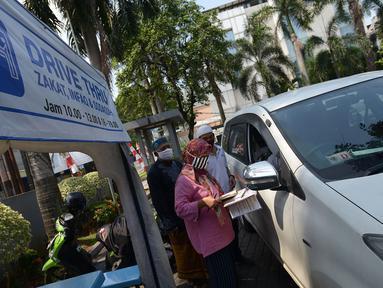 Panitia zakat fitra melakukan pengisian data di Masjid Nurul Hidaya, Jakarta, Sabtu (16/5/2020). Di tengah pandemi Covid-19 panitia masjid membuat lokasi penerima zakat dengan drive thru. (merdeka.com/Imam Buhori)