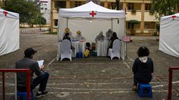 Penduduk memakai masker mengantre dengan tertib saat akan mengikuti pengujian Covid-19 di pusat pengujian darurat di Hanoi, Vietnam (31/3/2020). Di pusat pengujian darurat ini petugas menyediakan fasilitas bangku kecil yang diberi jarak untuk pencegahan Covid-19. (AFP/Manan Vatsyayana)