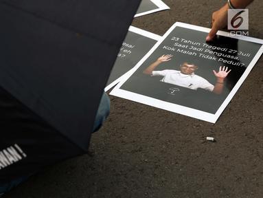 Aktivis yang tergabung dalam Jaringan Solidaritas Korban untuk Keadilan mengambil poster saat aksi Kamisan di depan Istana Negara, Jakarta, Kamis (25/7/2019). Aksi Kamisan ke-594 mengangkat tema '23 Tahun Tragedi 27 Juli Saat Jadi Penguasa Kok Malah Tidak Peduli?'. (Liputan6.com/Helmi Fithriansyah)