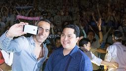 Youri Djorkaeff dan Erick Thohir foto bersama dengan latar belakang ramainya peserta Gathering Nasional Inter Club Indonesia ke-4 di GWK, Bali, Sabtu (29/8/2015). (Bola.com/Vitalis Yogi Trisna)