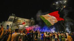 Suporter merayakan kemenangan Italia atas Inggris pada pertandingan final Euro 2020 di Roma, Italia, Senin (12/7/2021). Italia menjuarai Euro 2020 usai mengalahkan Inggris lewat drama adu penalti pada pertandingan final. (AP Photo/Alessandra Tarantino)