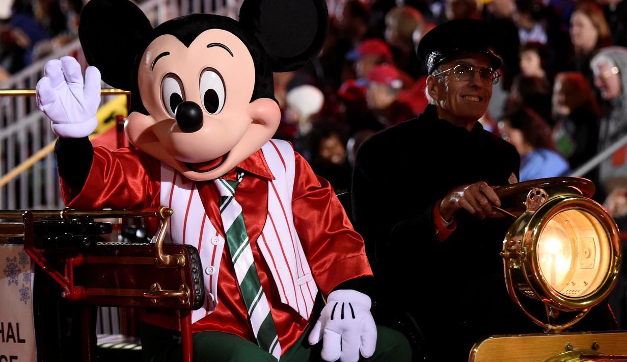 Karakter Mickey Mouse menaiki mobil saat mengikuti Parade Natal Hollywood ke-85 di Los Angeles, California, AS (27/11). Parade ini dirayakan tiap tahunnya untuk menyambut datangnya Hari Raya Natal. (Reuters/Phil McCarten)