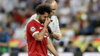 Pemain depan Liverpool Mohamed Salah meninggalkan lapangan sambil menangis usai cedera saat melawan Real Madrid dalam pertandingan final Liga Champions di Stadion NSK Olimpiyskiy, Ukraina (26/5). (AP / Matthias Schrader)
