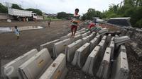 Anak-anak bermain diatas beton di sekitar pembangunan Taman Bersih Manusiawi dan Wibawa (BMW) di Jakarta Utara, Selasa (7/3). Pemprov DKI Jakarta akan melanjutkan kembali pembangunan taman dan stadion BMW. (Liputan6.com/Immanuel Antonius)