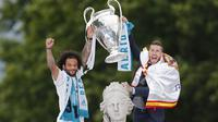 Pemain Real Madrid, Sergio Ramos dan Marcelo, mengangkat trofi Liga Champions di Monumen Cibeles, Madrid, Minggu (27/5/2018). Real Madrid menggelar pawai kemenangan bersama fans usai menjuarai Liga Champions 2018. (AP/Francisco Seco)