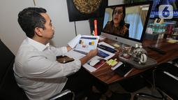 Anggota DPR Komisi XI Bidang Keuangan & Perbankan Kamrussamad dalam Rapat Dengar Pendapat (RDP) dengan Menteri Keuangan, Sri Mulyani dari ruang kerjanya secara virtual di Jakarta, Senin (6/4/2020). RDP juga diikuti Gubernur BI, Ketua OJK dan Ketua LPS. (Liputan6.com/HO/Bon)