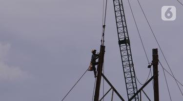 Pekerja tengah melakukan aktivitas kerja pada ketinggian di menara sutet di kawasan Karang Tengah, Kota Tangerang, Banten, Jumat (8/1/2021). Keselamatan dan kesehatan kerja (K3) merupakan hal yang mutlak bagi para pekerja di ketinggian dengan risiko tinggi. (Liputan6.com/Angga Yuniar)
