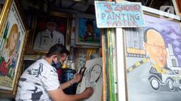 Seorang pelukis sedang menyelesaikan lukisan tokoh-tokoh nasional di Depan Pasar Baru, Jakarta, Kamis (24/12/2020). Di masa-masa awal pandemi para pelukis ini mengaku sepi pesanan, tapi kini mulai banyak pemesanan lukisan mulai tokoh nasional hingga para artis. (merdeka.com/Dwi Narwoko)