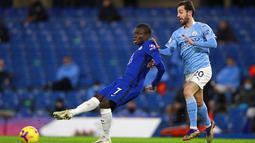 Pemain Chelsea N'Golo Kante mengoper bola saat pemain Manchester City Bernardo Silva mencoba mengganggunya pada pertandingan Liga Inggris di Stamford Bridge, London, Inggris, Minggu (3/1/2021). Manchester City mempermalukan Chelsea dengan skor 3-1. (AP Photo/Ian Walton/Pool)