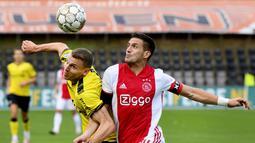 Striker Ajax Amsterdam, Dusan Tadic, berebut bola dengan pemain VVV-Venlo, Tobias Pachonik, pada laga Eredivisie di Stadion De Koel, Minggu (25/10/2020). Ajax Amsterdam menang dengan skor 13-0. (AFP/Olaf Kraak)