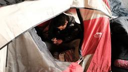 Seorang pria menggunakan heroin di dalam tendanya di kawasan yang menjadi pusat penggunaan heroin di Kensington, Philadelphia (24/1). DEA juga menjelaskan lebih dari 900 orang meninggal pada tahun 2016 akibat overdosis. (Spencer Platt/Getty Images/AFP)