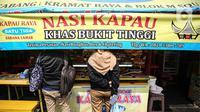 Suasana warung nasi kapau di kawasan Senen, Jakarta Pusat, Senin (19/10/2020). Pelonggaran pembatasan sosial berskala besar (PSBB) kembali ke fase transisi disambut baik oleh para pelaku usaha kuliner karena pengunjung dapat kembali bersantap di tempat. (Liputan6.com/Faizal Fanani)