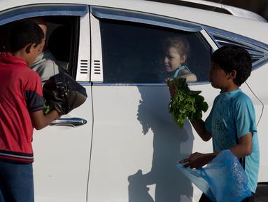Anak-anak Palestina menjual sayuran untuk membantu keluarga mereka menghasilkan sedikit uang selama bulan suci Ramadhan di Gaza (19/5/2019). Umat Muslim di seluruh dunia tengah melaksanakan puasa dimana mereka tidak makan, minum mulai dari matahari terbit hingga terbenam. (AP Photo/Hatem Moussa)