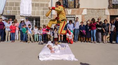 Pria berkostum setan melompati bayi-bayi yang diletakkan di atas matras selama tradisi El Salto del Colacho di desa Castrillo de Murcia, Spanyol, Minggu (3/6). Festival melompati bayi ini sudah menjadi perayaan tahunan sejak 1620 (afp/CESAR MANSO)