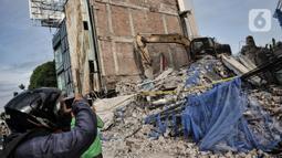 Warga mengabadikan kondisi bangunan yang roboh di Jalan Kyai Caringing, Gambir, Jakarta, Kamis (3/9/2020). Bangunan empat lantai itu roboh dan menimpa kabel listrik serta reruntuhannya menutupi jalan sehingga arus kendaraan arah Harmoni-Grogol sempat dialihkan. (merdeka.com/Iqbal Nugroho)