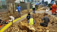 Sejumlah pekerja membersihkan sisa sisa bekas tebangan pohon di trotoar Cikini. ((Liputan6.com/ Rizki Putra Aslendra))