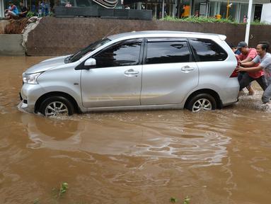 Sejumlah orang memindahkan mobil yang terendam banjir di kawasan Kemang, Jakarta, Kamis (2/1/2020). Banjir yang melanda Jakarta dan sekitarnya mengakibatkan banyak kendaraan terendam air. (Liputan6.com/Herman Zakharia)