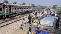 Tentara dan pejabat Pakistan memeriksa kereta yang rusak akibat kebakaran di Liaquatpur, Pakistan (31/10/2019). Insiden terjadi pada kereta yang dikenal sebagai Tezgam Espress. Kereta itu melakukan perjalanan ke berbagai kota antara daerah Karachi dan Rawalpindi.  (AP Photo/Siddique Baluch)