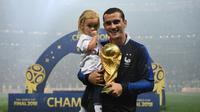 Pemain depan Prancis, Antoine Griezmann berpose dengan putrinya sambil membawa trofi Piala Dunia di Stadion Luzhniki, Moskow, Rusia, 15 Juli 2018. Griezmann masuk dalam kandidat pemain terbaik FIFA 2018. (AFP FOTO/FRANCK FIFE)