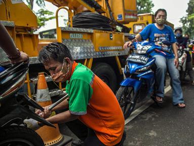 Petugas mengecek emisi gas buang kendaraan bermotor di Jakarta, Rabu (6/1/2021). Pengecekan yang diselenggarakan Dinas Perhubungan dan Kepolisian tersebut bertujuan untuk mengurangi polusi udara dari emisi gas buang kotor. (Liputan6.com/Faizal Fanani)