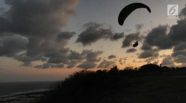 Wisatawan melakukan tandem paralayang di Bukit Riug, Nusa Dua, Bali (30/6). Kegiatan paralayang tandem dengan mengandalkan angin pantai sudah lebih dari satu tahun digemari para wisatawan mancanegara dan lokal. (Merdeka.com/Arie Basuki)