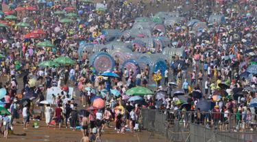 Wisatawan memadati pantai untuk mendinginkan diri di Qingdao, China timur, pada 3 Agustus 2019. Banyak warga di Negeri Tirai Bambu memanfaatkan musim panas dengan mengunjungi pantai untuk mengisi liburan. (Photo by FRED DUFOUR / AFP)