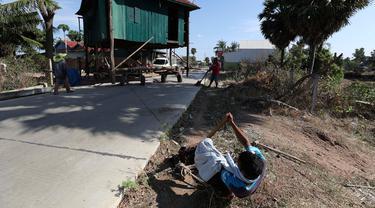 Seorang pria menarik rumah kayu ke tempat di desa Pon Sang di sisi utara Phnom Penh, Kamboja (26/4/2020). Ini adalah cara bergerak tradisional yang dikumpulkan oleh penduduk desa untuk saling membantu dengan menggunakan traktor dan batang kayu. dengan menjaga rumah tetap utuh. (AP/Heng Sinith)