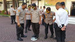 Personel kepolisian saat diukur berat badan usai apel pagi di lapangan apel Mapolda Gorontalo, Senin (13/5/2019). Kegiatan ini merupakan tindak lanjut program dari Mabes Polri yang mencanangkan program pengendalian berat badan bagi personel Polri. (Liputan6.com/Arfandi Ibrahim)